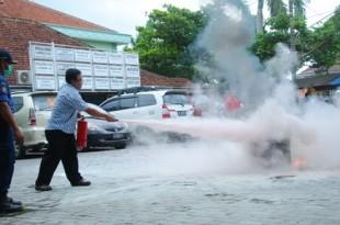 Direktur Administrasi dan Keuangan RSCH Made Sumiarta memperagakan APAR untuk memadamkan api.